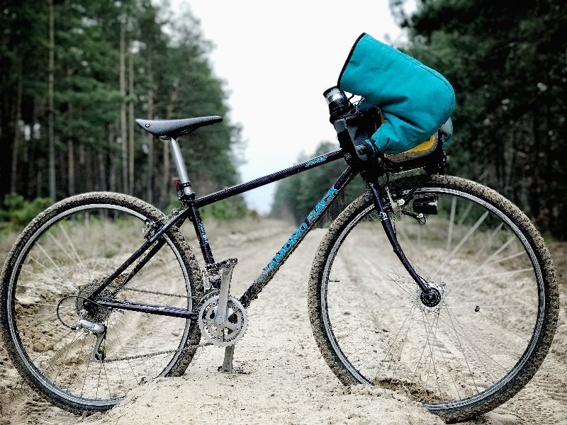 Bikepacking bicycle on the sandy road with handlebar winter cycling pogies and Dandy bag
